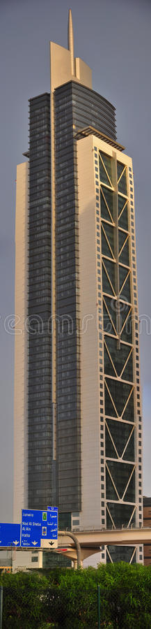 Dubai Tower with sign board. Huge building in front of Burj Dubai, with metro track and road sign board royalty free stock photo