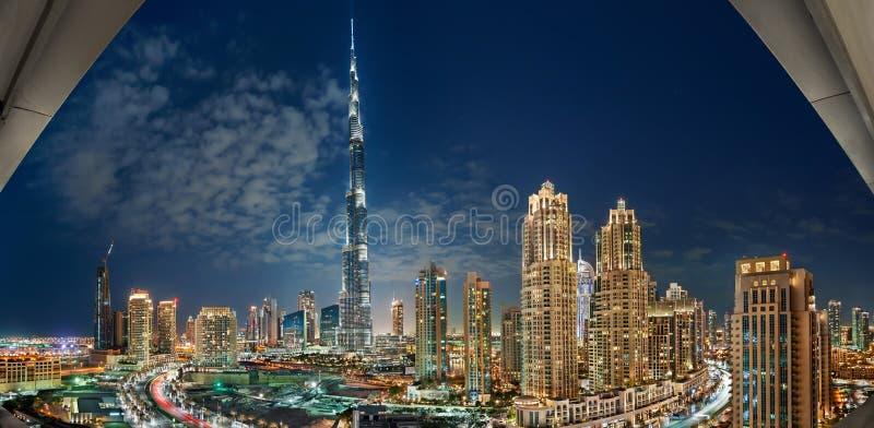 DUBAI-UAE, 31-ое декабря 2013: Burj Khalifa окруженное Дубай к центру города возвышается на ноче стоковые фотографии rf