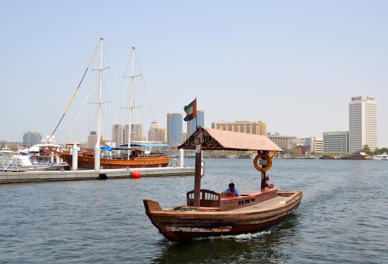 Traditional boat called abras and a view on Dubai creek with its modern buildings royalty free stock photos
