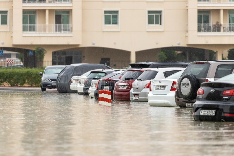 DUBAI, UAE - CIRCA 2020: Cars stuck in water in a flooded parking lot after heavy in rain in Dubai stock photo