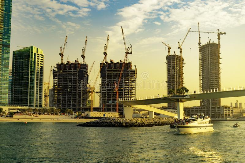 Dubai, UAE / 11. 10. 2018 : Dubai contractions on the coast line with cranes everywere in sunset stock photography