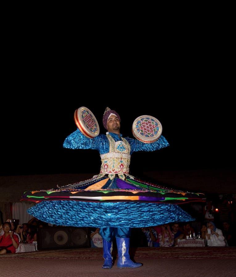 DUBAI, UAE - 20 DE ABRIL DE 2012: Un ciudadano local que realiza danza popular tradicional en la noche como parte de una experien imagen de archivo