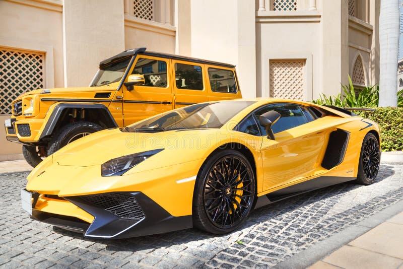 DUBAI, UAE - 8 DE JANEIRO DE 2019: supercarro luxuoso amarelo Lamborghini Aventador Roadster e Gelandewagen em Dubai imagem de stock