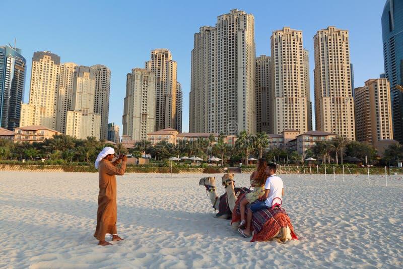 DUBAI, UAE - 23 DE NOVEMBRO DE 2017: Os turistas montam camelos na frente de Jumeirah Beach Residence em Dubai, Emiratos Árabes U imagens de stock royalty free
