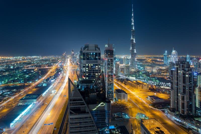 DUBAI UAE - DECEMBER 17, 2015: Flyg- sikt av Dubais i stadens centrum arkitektur på natten med och Burj Khalifa royaltyfria bilder
