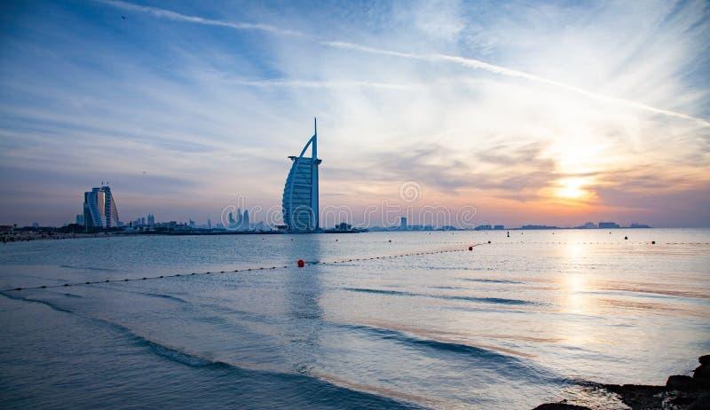 DUBAI, UAE - EM FEVEREIRO DE 2018: Hotel de luxo Burj Al Arab das sete estrelas do mundo o primeiro na noite vista da praia públ foto de stock royalty free