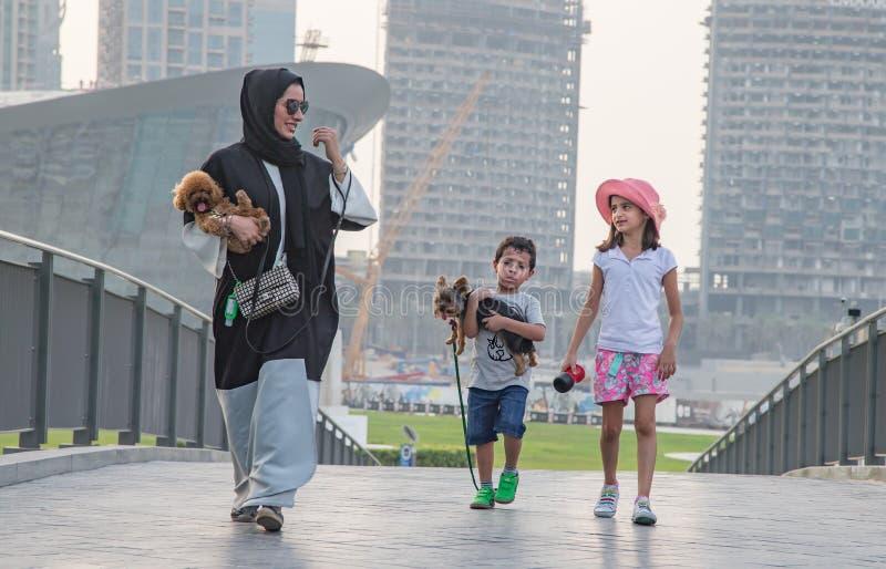 Dubai, UAE, em julho de 2016: família que anda as ruas de Dubai foto de stock royalty free