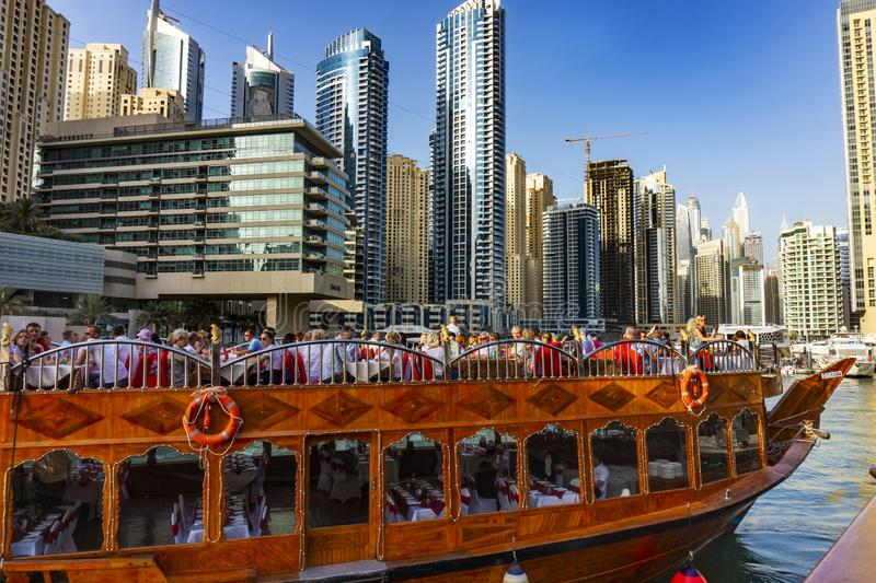 Dubai, UAE / 11. 10. 2018 : Famous traditional wooden old dhow cruise tour in the marina with tourist on the board and modern royalty free stock photography