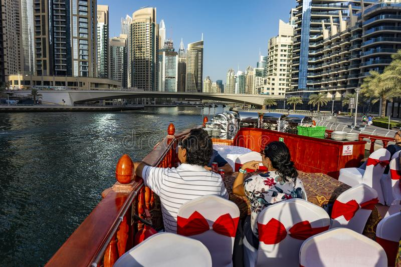 Dubai, UAE / 11. 10. 2018 : Famous traditional wooden old dhow cruise tour in the marina with tourist on the board and modern stock image