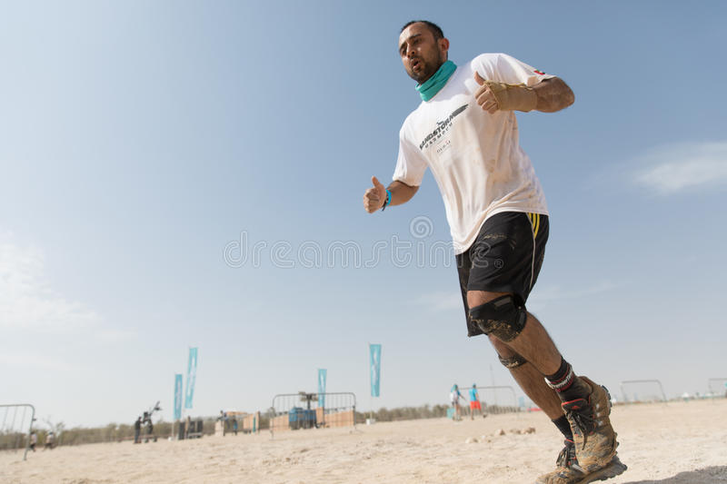 Dubai, UAE - Feb 10, 2017: Participant competing on an obstacle course. Competitor participating an off-track obstacle running competition royalty free stock images