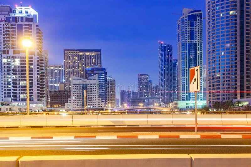 DUBAI, UAE - FEBRERO DE 2018: Vista de los rascacielos modernos que brillan en luces de la salida del sol en el puerto deportivo  fotos de archivo
