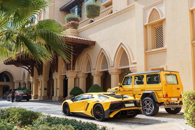 DUBAI, UAE - 8. JANUAR 2019: gelber Luxussupercar Lamborghini Aventador Roadster und Gelandewagen in Dubai lizenzfreies stockbild