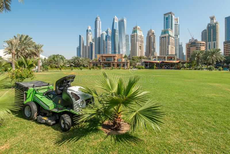 Dubai, UAE - January 12, 2019: Lawn mowing tractor on a green field in front of the skyscrapers of Dubai Marina. & royalty free stock images