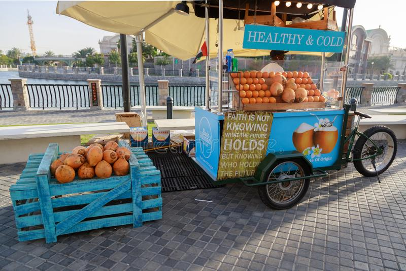 Street vendor sells fresh oranges and coconut using a mobile bicycle cart. DUBAI, UAE, JANUARY 09, 2019: Street vendor sells fresh oranges and coconut using a stock photography