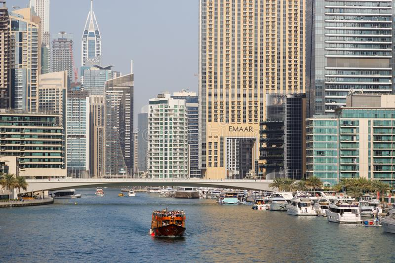 Wooden touristic ship sails on the bay against the background of modern buildings in the district of Dubai Marina royalty free stock image