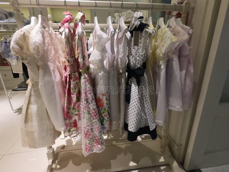 Dubai UAE - Juli 2019: En rad av barnkläder som hänger på hängare Barn som beklär inom för att shoppa En sikt av den färgglade un arkivbilder