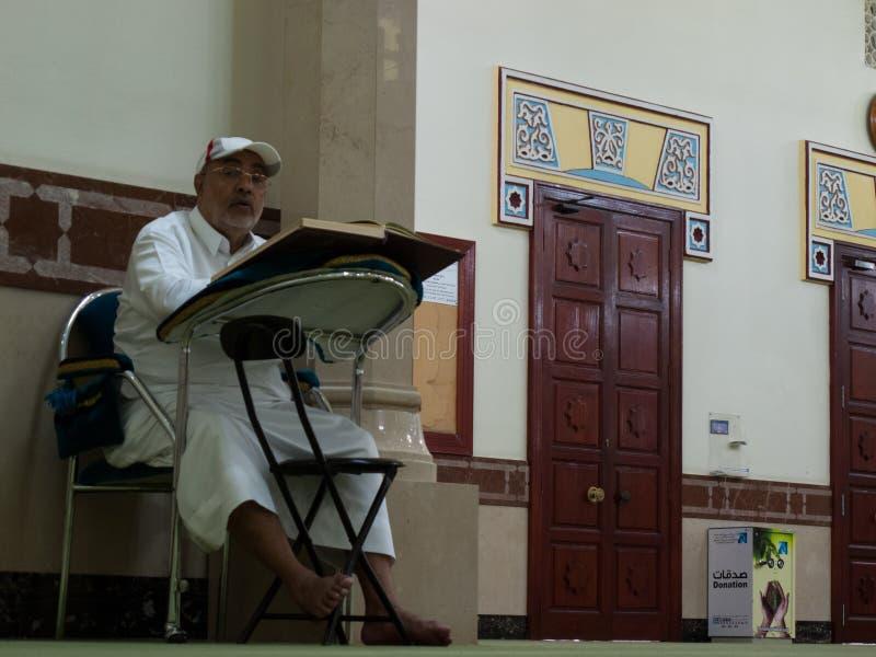 Dubai, UAE - março, 03, 2017: Um homem que lê o livro do koran em uma mesquita em Dubai imagens de stock