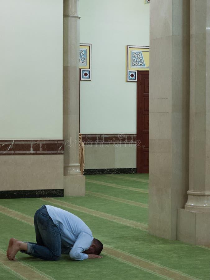 Dubai, UAE - março, 03, 2017: Um homem que reza em uma mesquita em Dubai imagens de stock royalty free