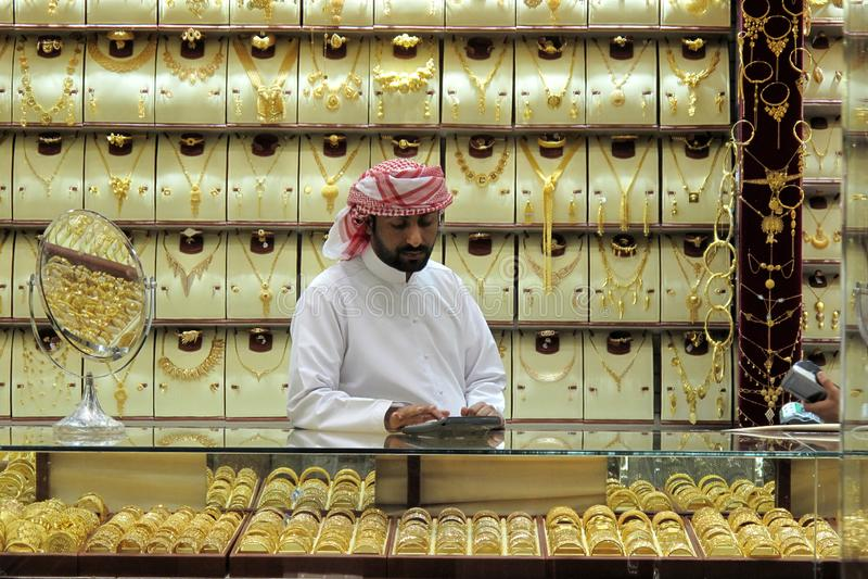 Dubai, UAE - marzo, 03, 2017: Vendedor del oro dentro de una joyería en el souk del oro de Dubai imagen de archivo libre de regalías