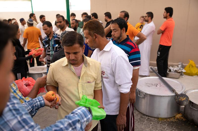 Food packages` distribution in mosque during Ramadan iftar meal. Dubai, UAE - May 18, 2018: Volunteers distributing food packages to workers during iftar meal royalty free stock photo