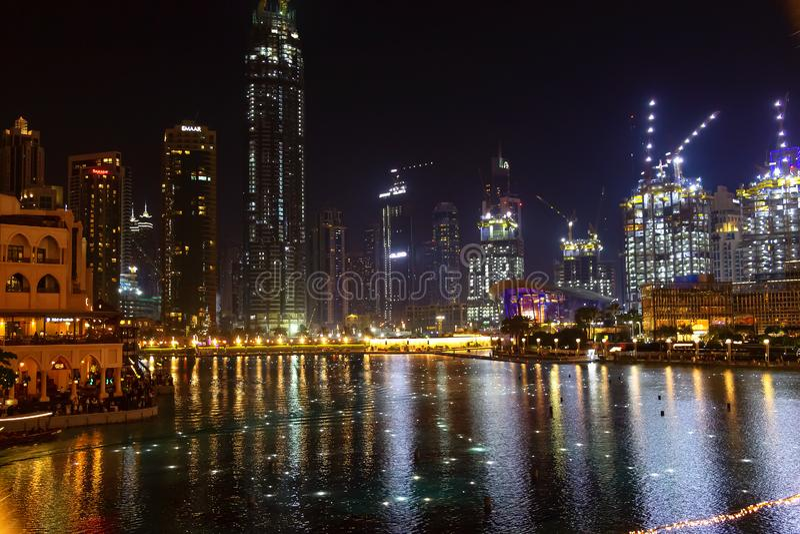 Dubai, UAE - mayo de 2019: Las luces que brillan intensamente riegan con poca agua la piscina de la fuente del baile del sistema  fotografía de archivo libre de regalías
