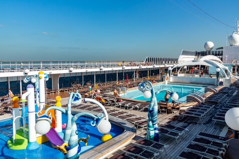 Dubai, United Arab Emirates - December 12, 2018: cruise ship upper deck with swimming pool and resting passengers.  royalty free stock images