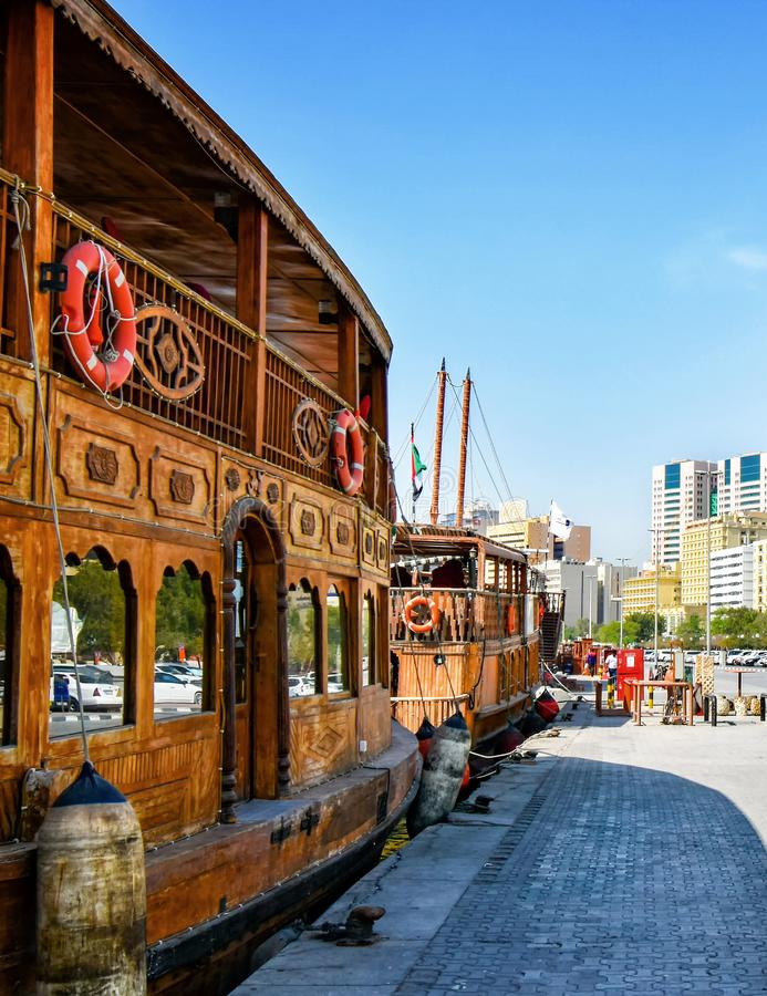 Traditional wooden Dhows are moored on the banks of the Creek in Dubai. Dubai, United Arab Emirates – February 13, 2018: Traditional wooden Dhows are royalty free stock images