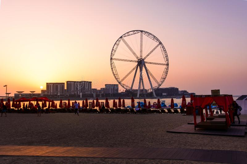 Dubai, United Arab Emirates - March 8, 2018: Sunbeds and romantic sunset at JBR, Jumeira Beach Resort beach with ferris wheel in royalty free stock photos