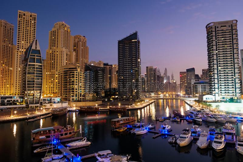 Dubaj marina z łodziami i budynkami z bramami przy nocą z światłami i niebieskim niebem fotografia stock