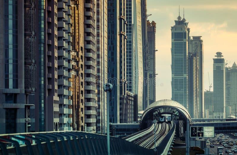 DUBAJ, UAE - GRUDZIEŃ 16, 2015: Dubaj nowożytna architektura przy zmierzchem z stacją metru zdjęcie stock