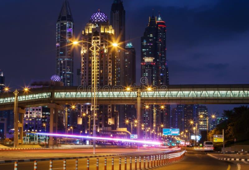 DUBAJ, UAE - GRUDZIEŃ 15, 2015: Iluminująca nowożytna architektura Dubaj Marina nocą Widok Marina Góruje z autostradą obraz royalty free