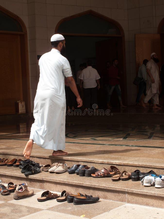 Dubaj, UAE - Marzec, 03, 2017: Mężczyzna wchodzić do meczet modlitewny wezwanie, opuszcza buty w wejściu zdjęcie stock