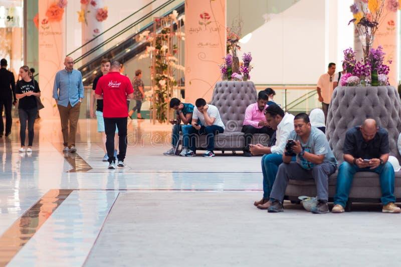 DUBAJ ZJEDNOCZONE EMIRATY ARABSKIE, KWIECIEŃ, - 25, 2018: Zanudzający mężczyźni czekać na kobiety kończyć robić zakupy, wewnętrzn obraz royalty free