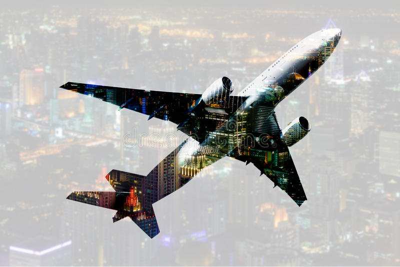 Dubbel blootstellings commercieel vliegtuig met onduidelijk beeldcityscape backgrou stock foto
