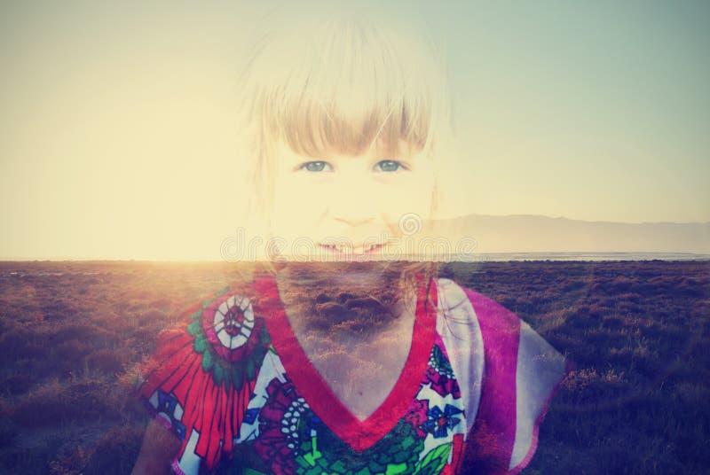 Dubbel blootstellingsbeeld van een kleine van de blondemeisje en zomer zonsondergang; retro styele stock foto's