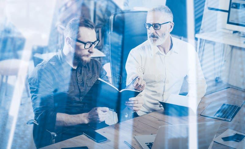 Dubbel blootstellingsconcept Groepswerkproces in moderne coworking studio Jonge gebaarde mens en volwassen zakenman die nota's ma stock afbeeldingen