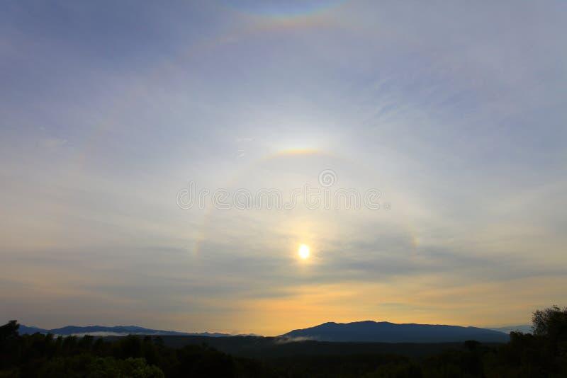 Dubbel cirkel av solglorien över berget under den guld- timmen av soluppgång royaltyfri foto