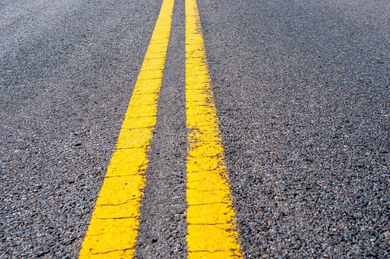 Dubbel delande linje för guling över svart huvudvägasfalt royaltyfria foton