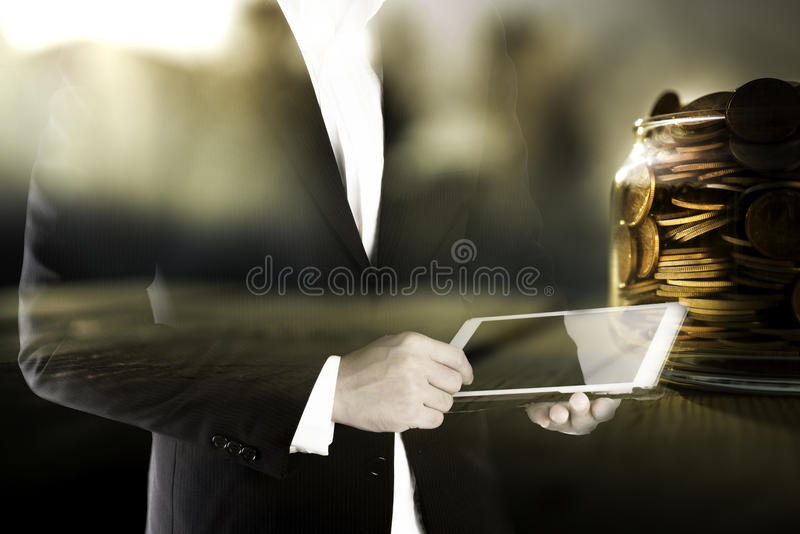 Dubbel exponering av affärsmannen som använder minnestavlan, och guld- mynt, i krus, teknologi och att packa ihop investeringbegr royaltyfri foto