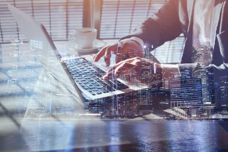 Dubbel exponering av affärsmannen som direktanslutet upp arbetar på bärbar datordatoren, slut av händer arkivfoto