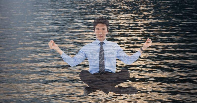 Dubbel exponering av affärsmannen som gör yoga över havet arkivbilder