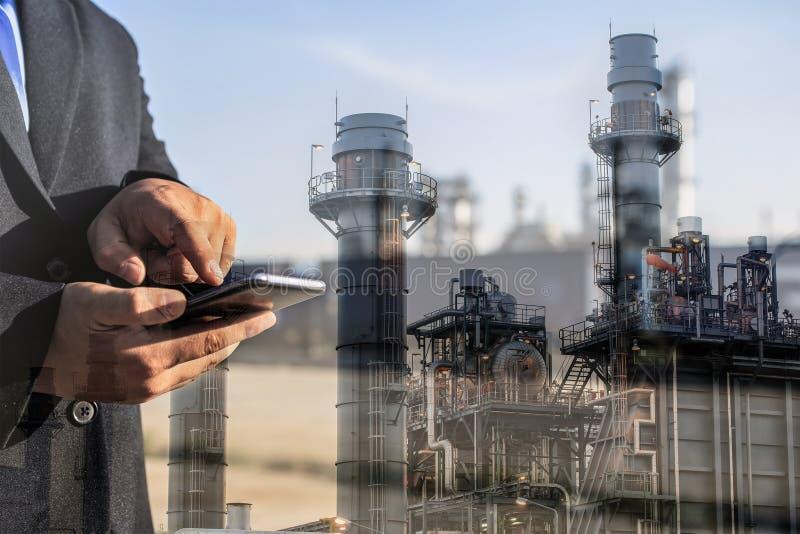 Dubbel exponering av affärsmannen som kontrollerar oljeraffinaderibranschväxten vid den smarta telefonen royaltyfri fotografi
