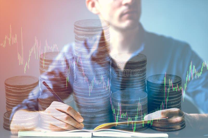 Dubbel exponering av affärsmannen som vrida sig på skrivbord- och aktiemarknad- eller forexgraf, och bunten myntar passande för f arkivbild