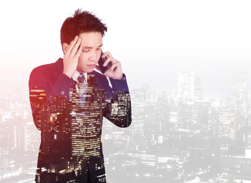 Dubbel exponering av den bekymrade affärsmannen som talar på smartphonen med en stad royaltyfri foto