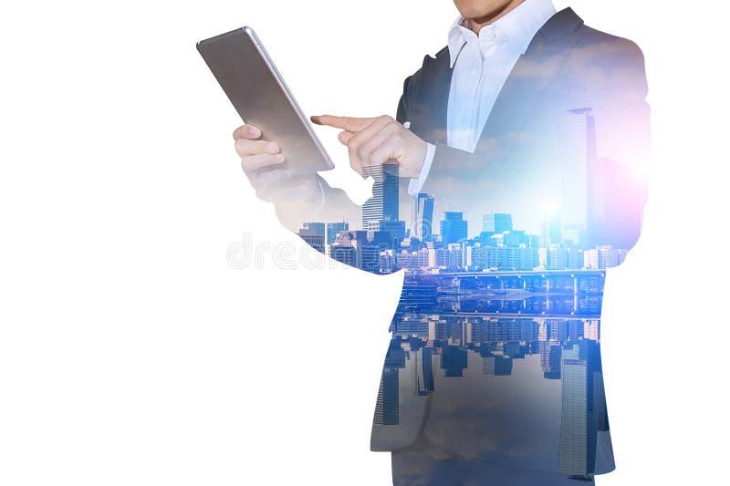 Dubbel exponering av den hållande minnestavlan för affärsman med suddig bakgrund för cityscape arkivfoto