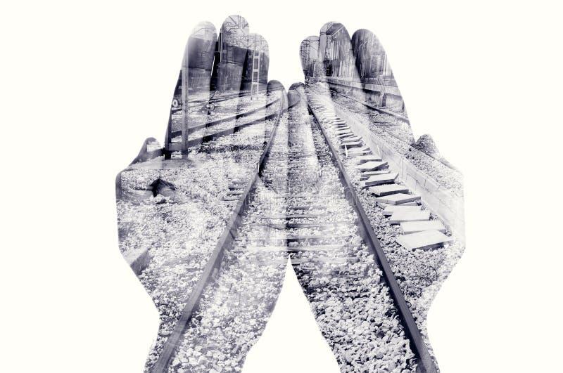 Dubbel exponering av den manhänder och järnvägen, i svartvitt royaltyfri fotografi