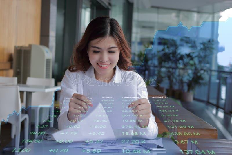 Dubbel exponering av den unga attraktiva affärskvinnan som ser dokumentet på skrivbordsarbete mot visningtillväxtdiagram på bakgr royaltyfri foto