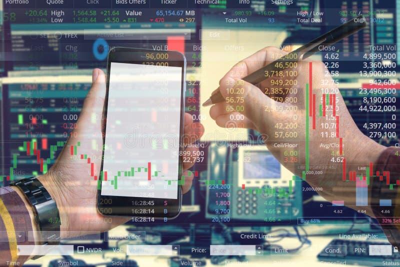 Dubbel exponering av handen av affärsmannen som använder smartphonen med materielhandelrum och, lagerför handeldiagrambakgrund fö arkivfoto