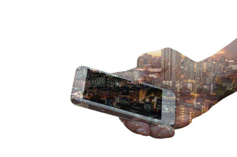 Dubbel exponering av handhållsmartphonen över nattstad arkivfoto