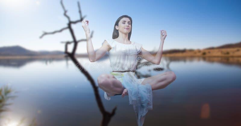Dubbel exponering av kvinnan som mediterar över sjön fotografering för bildbyråer